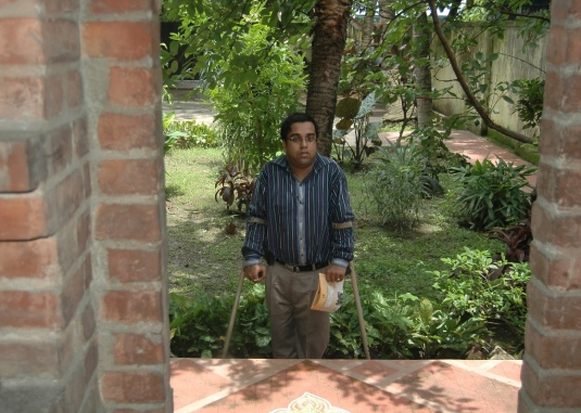 Sudipendu Dutta on crutches standing outside inaccessible meditation building